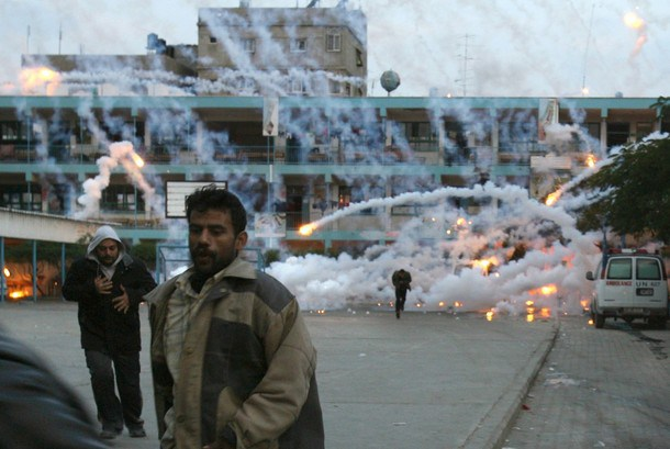 Palestinian civilians and medics run to safety during an Israeli strike over a UN school in Beit Lahia, northern Gaza Strip early on January 17, 2009. A woman and a child were killed early today in the Israeli strike on the UN-run school in northern Gaza where civilians were sheltering from the fighting, medics and witnesses said. Fierce clashes were underway around the school as Israeli tanks exchanged fire with Palestinian militants, they said. AFP PHOTO / MOHAMMED ABED ALTERNATIVE CROP (Photo credit should read MOHAMMED ABED/AFP/Getty Images)