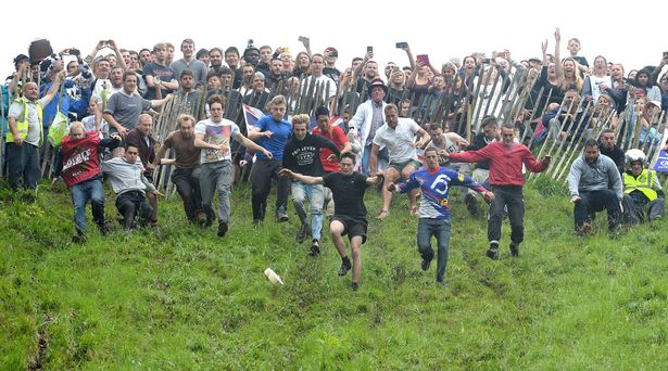 Competitors Take Part In The Annual Unofficial Cheese Rolling At Coopers Hill In Brockworth