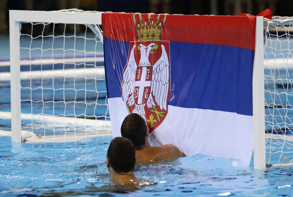 Member of the Serbia men's water polo team kiss a state flag as they celebrate their victory during men's gold medal water polo match against Croatia at the 2016 Summer Olympics in Rio de Janeiro, Brazil, Saturday, Aug. 20, 2016. (AP Photo/Sergei Grits)