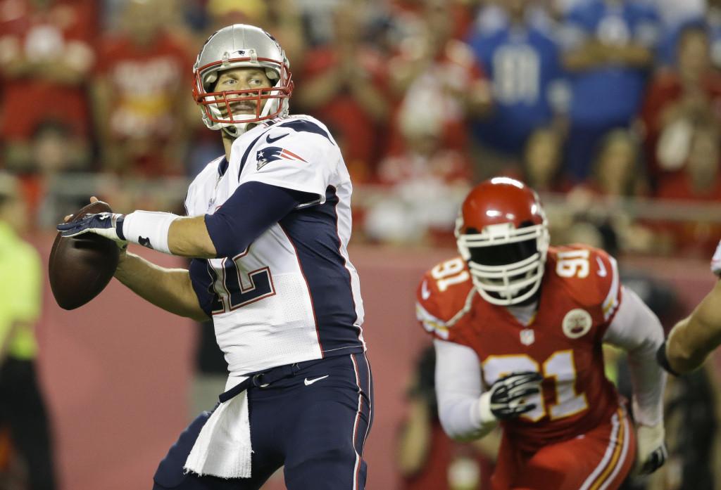 New England Patriots quarterback Tom Brady, left, throws as Kansas City Chiefs linebacker Tamba Hali, right, defends during the first quarter of an NFL football game Monday, Sept. 29, 2014, in Kansas City, Mo. (AP Photo/Nati Harnik)