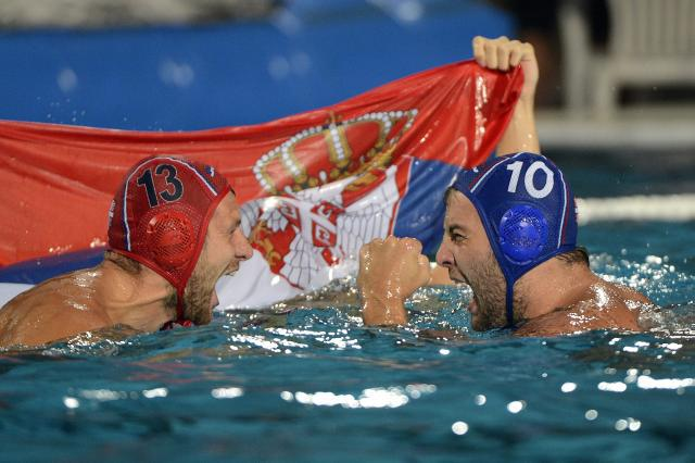 Branislav Mitrovic, left, and Filip Filipovic of Serbia celebrate with a Serbian flag after defeating Hungary in the men's final of European Water Polo Championships in Hajos Alfred Swimming Pool in Budapest, Hungary, Sunday, July 27, 2014. (AP Photo/MTI, Tamas Kovacs)