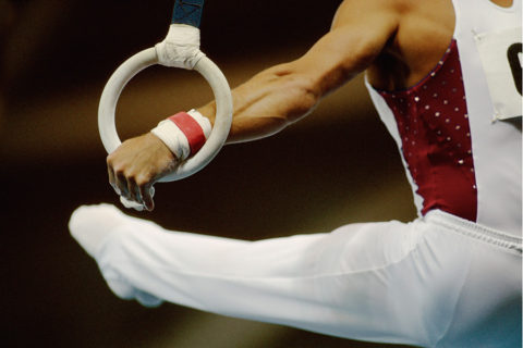Male gymnast performing on rings, close-up