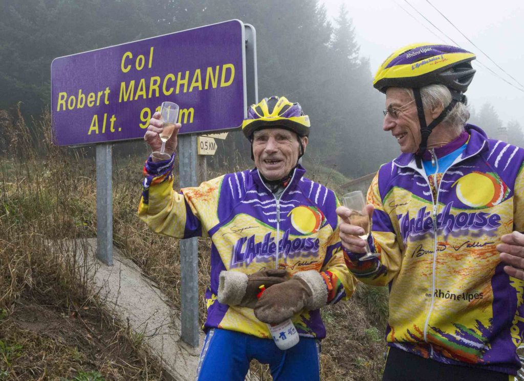 French cyclist Robert Marchand, raises a glass of champagne to celebrate his 103rd birthday as he poses near a sign along the Robert Marchand pass, in the Ardeche mountains, near Saint-Felicien