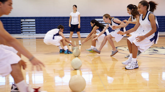 High School Students Playing Dodge Ball In Gymnasium